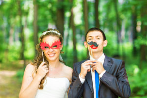 Wedding couple posing with stick lips, mask. April Fools' Day.